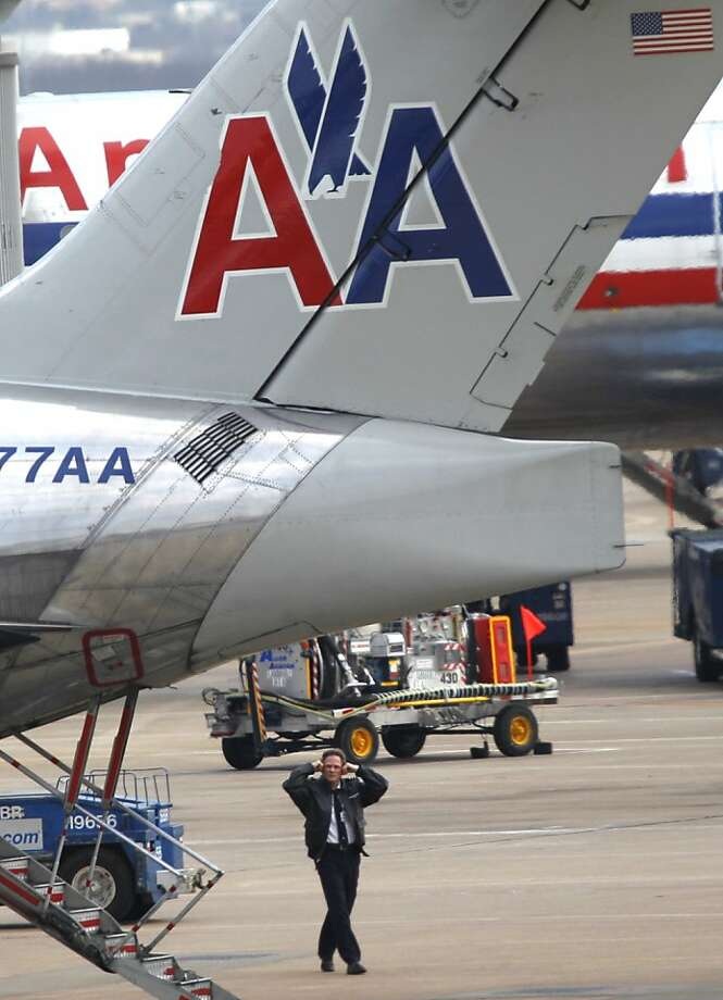 An American Airlines pilot covers his ears against engine noise as he visual inspects an aircraft before departure at Dallas-Fort Worth International airport in Grapevine, Texas, Wednesday, Feb. 1, 2012. (AP Photo/LM  Otero) Photo: LM  Otero, Associated Press