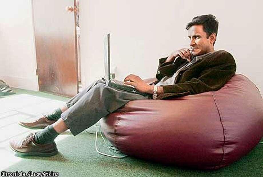 Suresh Reddy, 34, sits in his beanbag chair and works on his laptop, Thursday April 5, 01, in his office in San Francsico. He is one of the Asians that lives in Fremont and works in the city.  Photo By Lacy Atkins/San Francisco Chronicle Photo: Lacy Atkins