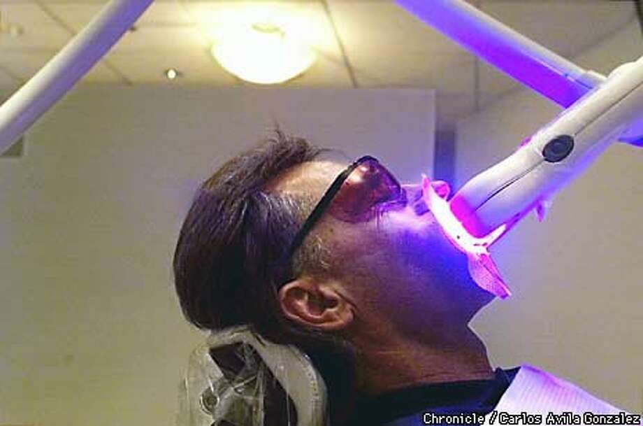 Richards wore orange goggles as a protective gel was applied to his gums. Chronicle Photo by Carlos Avila Gonzalez