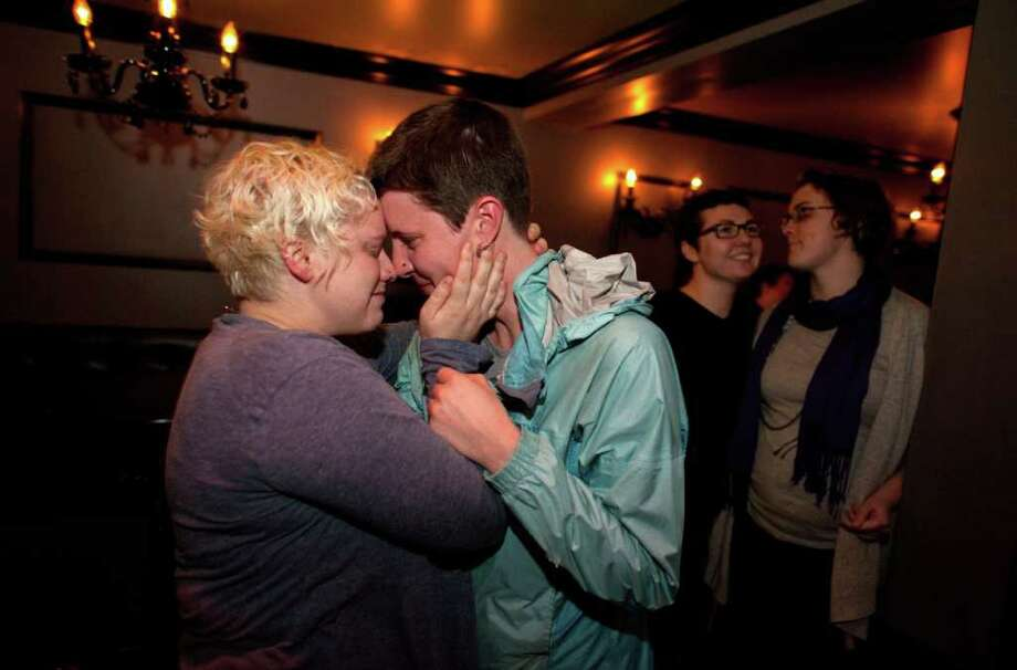 Kara Haney, left, and her partner of 8 years Kate Wertin, right, embrace in the Lobby Bar in Seattle's Capitol Hill neighborhood as the Washington State Senate passes a bill that would legalize gay marriage in Washington State on Wednesday, February 1, 2012. Dozens gathered at the bar to watch the debate via TV on the senate floor. Photo: JOSHUA TRUJILLO / SEATTLEPI.COM