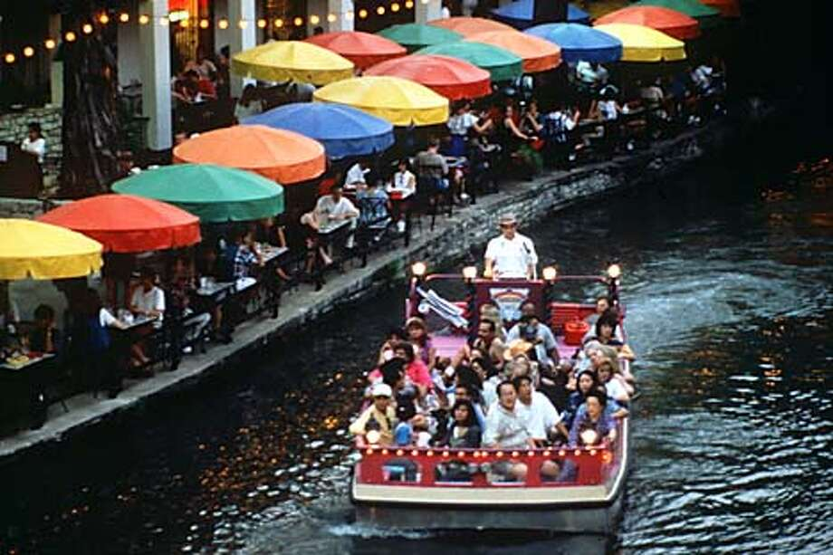 Passengers ride the San Antonio River next to Paseo del Rio, or Riverwalk, the city's tourist district.  Photo by Craig Stafford of the San Antonio Convention and Visitors Bureau