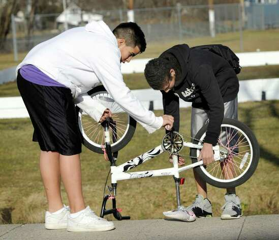 Chris Rodriguez, 13, left, gets help from his friend, Kenneth Rios, 14, fixing his bike when it broke down on the way home from school Wednesday. The boys are students at Rogers Park Middle School in Danbury. Photo taken Wednesday, February 1, 2012. Photo: Carol Kaliff / The News-Times