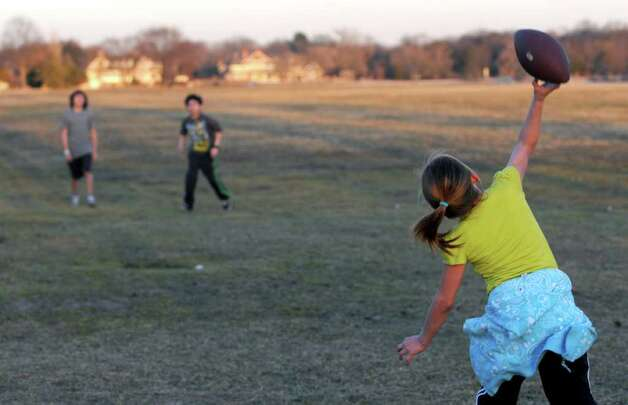 Daniella Ramirez, 9, throws a football with her brothers, Dereck, 10, and John, 12, at Cove Island Park on Tuesday, January 31, 2012. Photo: Lindsay Niegelberg / Stamford Advocate
