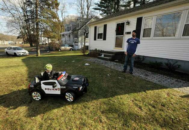 "Craig Palochick watches his son, Zac, 4, ride his toy car in their front yard in Bethel on Wednesday, February 1, 2012. Craig says, ""We were shoveling roofs this time last year. I'd much rather have this weather."" Photo: Jason Rearick / The News-Times"