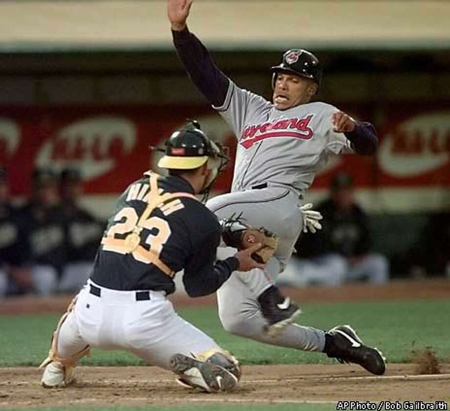 Cleveland Indians' David Justice slides past Oakland Athletics  catcher A.J. Hinch to score on a two-run double by teammate Einar Diaz  during the second inning Monday. AP Photo by Bob Galbraith