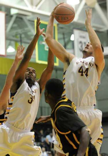 UAlbany's Jayson Guerrier, left, and John Puk go up for a rebound against UMBC during a basketball g