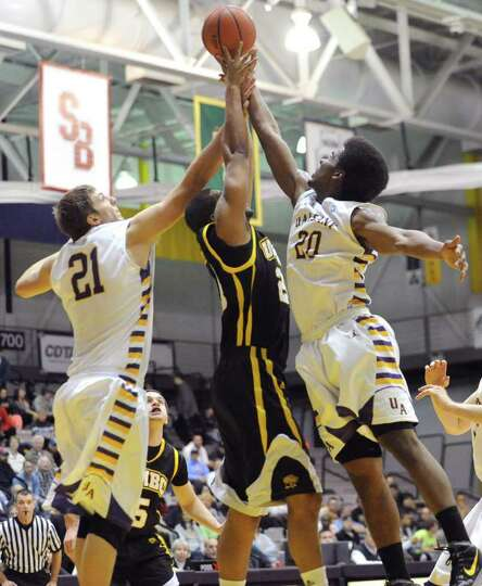 UAlbany's Blake Metcalf, left, and Gerardo Suero go up for a rebound with Will Wise of UMBC during a