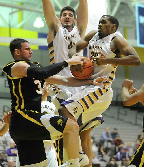 UAlbany's John Puk, center, and Jayson Guerrier try to come down with a rebound against UMBC's Jake