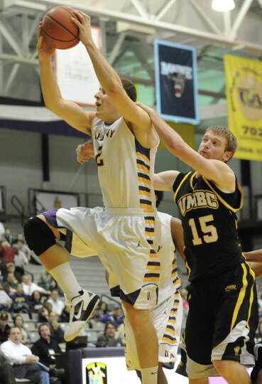UAlbany's Logan Aronhalt is fouled by UMBC's Brian Neller as he drives to the basket during a basket