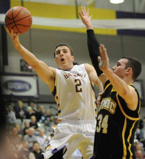 UAlbany's Logan Aronhalt drives to the basket against UMBC's Jake Wasco during a basketball game at
