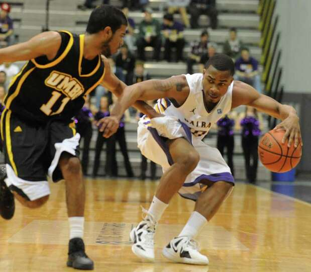 UAlbany's Mike Black is guarded by UMBC's Jarrel Lane as he dribbles the ball up the court during a