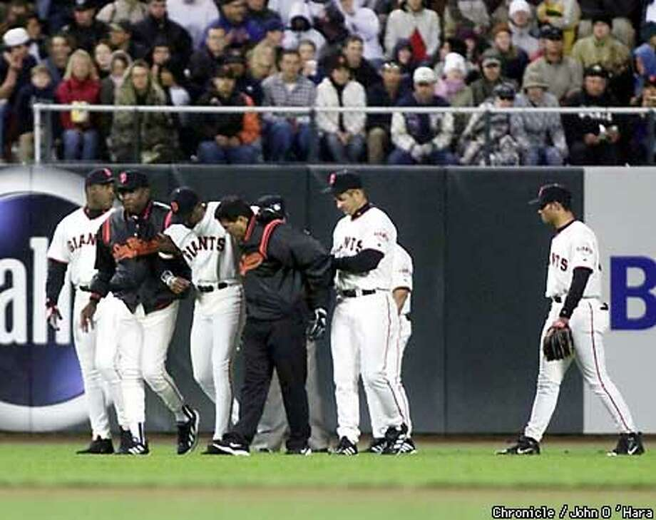 Pac Bell Park, San Francisco, CA.  Giants V/S Padres  T4 inning. Eric Davis RF injured himself and was helped off the field by DUsty Baker and a trainer along with other kteam mates  photo/John O'Hara Photo: JOHN O'HARA