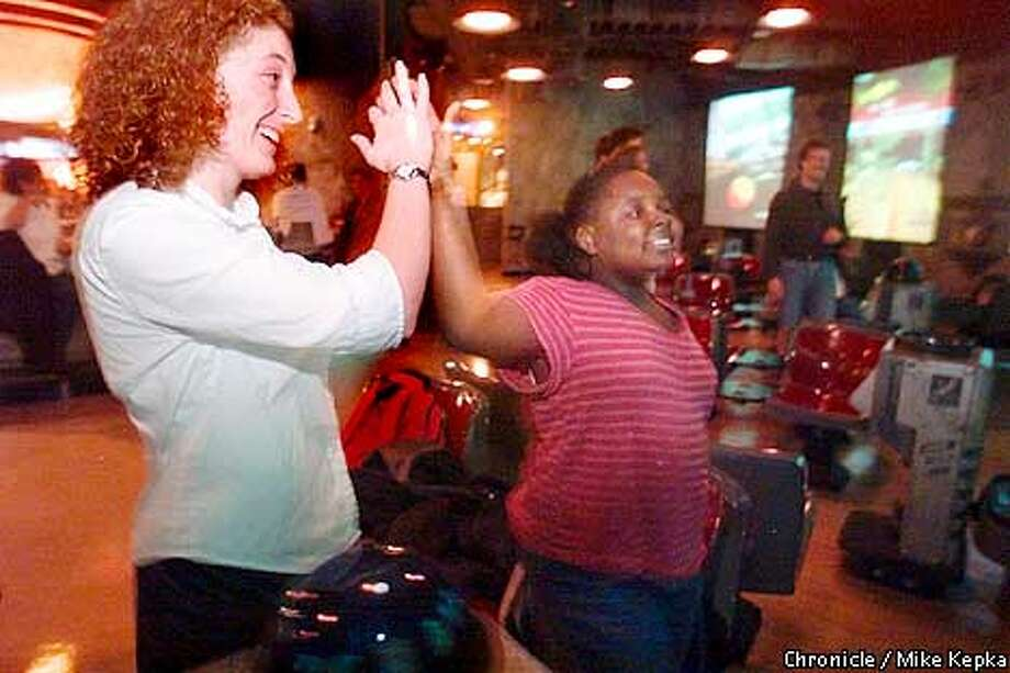 Mentor Alyssa Schwartz, gives a high five to her mentee Kristina Williams, 9, at the arcade at the Metreon. BY MIKE KEPKA/THE CHRONICLE Photo: MIKE KEPKA