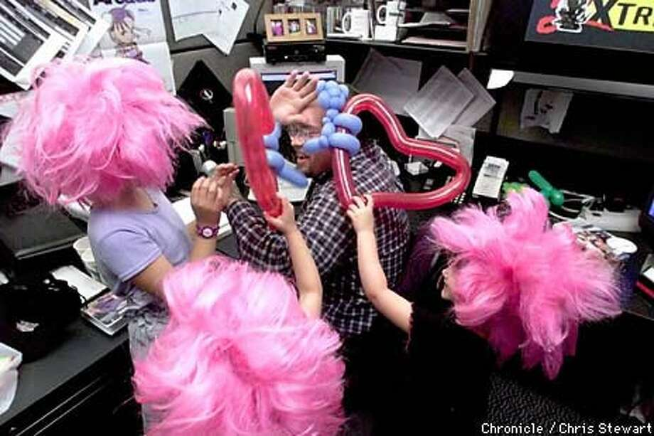 Kurtis Buckmaster, marketing Web master for Sony Computer Entertainment of America in Foster City, took a beating from his daughters Amanda Meacham (left), Tessa Meacham (middle) and Courtney Buckmaster. The girls wore pink wigs that resemble one worn by a video game character, Tomba. Chronicle Photo by Chris Stewart