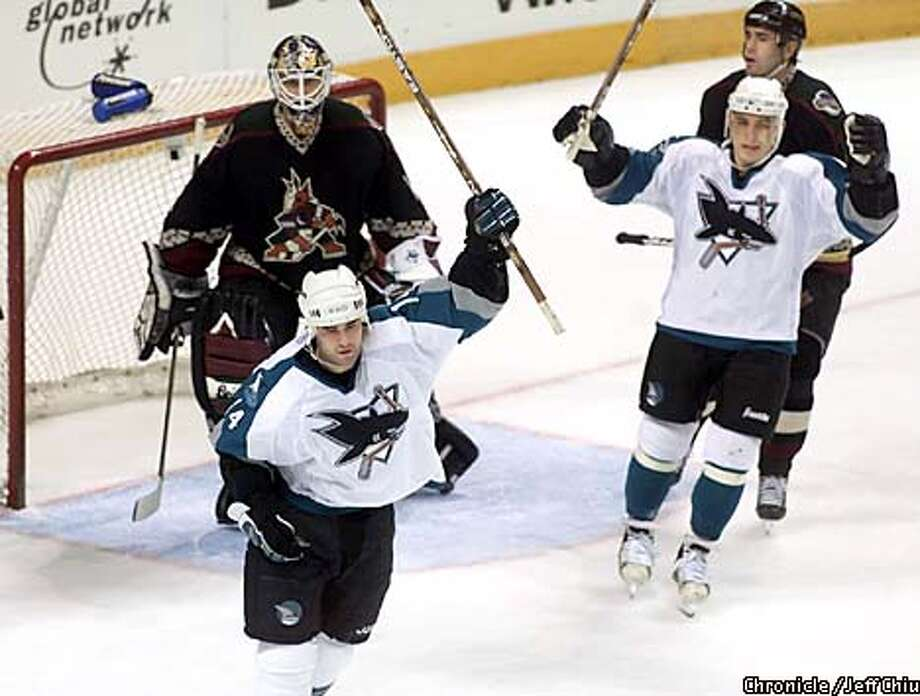 The Sharks' Patrick Marleau, front, celebrated with teammate Alexander Korolyuk after scoring a first-period goal. Chronicle photo by Jeff Chiu