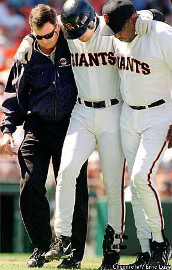 Ramon Martinez, who fouled a ball off his knee, was helped back to the dugout by Giants trainer Mark Letendre (left) and manager Dusty Baker. Chronicle Photo by Eric Luse