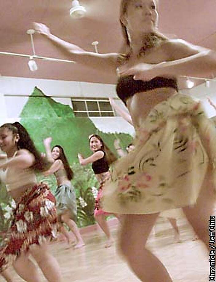 Hawaiian native Delisa Garcia and other dancers of Hula Halau 'O Ku'uleinani practice a Tahitian dance at the Halau 'O Ku'uleinani dance studio in San Carlos on Wednesday night. The group, led by Renee Ku'uleinani Price, will be performing at the Flint Center in Cupertino on Saturday, April 7. Photo by Jeff Chiu / The Chronicle. Photo: JEFF CHIU
