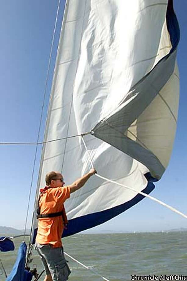 Andy Kopac, who met his wife at a Crew List party, adjusts the jib on his 38-foot ketch Soy Libre during a shakedown cruise Sunday on San Francisco Bay. The Kopacs hope to go blue-water sailing next year. Chronicle photo by Jeff Chiu