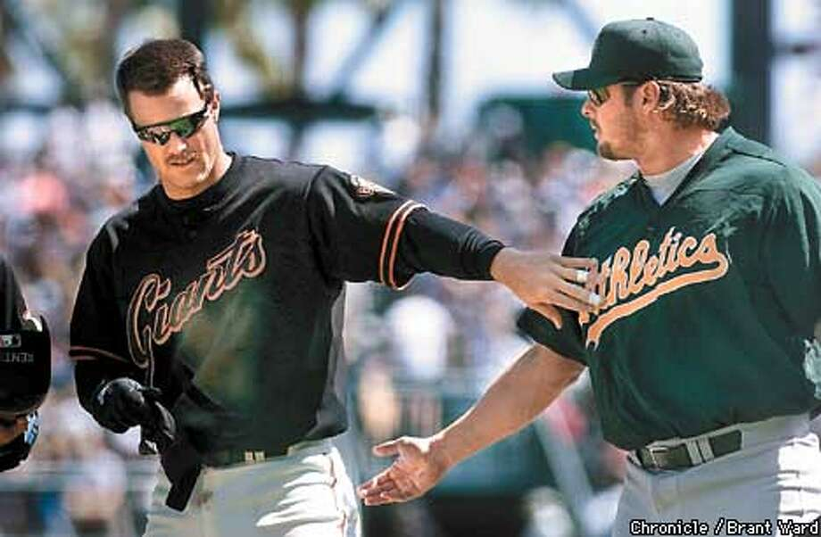 GIANTS3-01APR01-SP-BW--The MVP's from both leagues, Jeff Kent from the Giants and Jason Giambi from the A's exchanged pleasantries after the end of the first inning in the game Sunday. By Brant Ward/Chronicle Photo: BRANT WARD