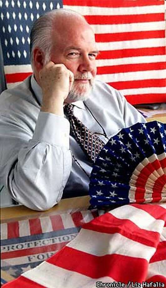 Kit Hinrichs, holding a turn-of-the-century crepe fan, has more than 2,500 items in his collection of American flag memorabilia, including the 50-star Navajo flag behind him and a 100-year-old silk flag on the table in front of him. Chronicle Photo by Liz Hafalia