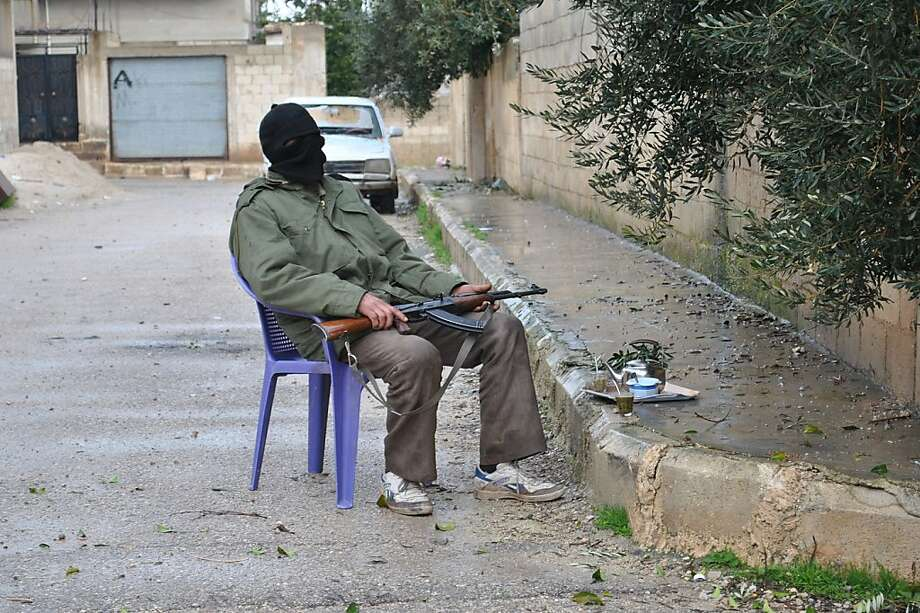A Syrian rebel guards an alley, at Rastan area in Homs province, central Syria, on Wednesday Feb. 1, 2012. Syrian troops battled army defectors in a string of towns in the mountains overlooking Damascus on Wednesday in a new assault to crush rebellious areas around the capital, activists said. Photo: Str, Associated Press