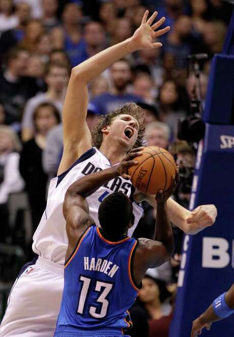 A rough game for the Mavericks' Dirk Nowitzki included taking a hit from the Thunder's James Harden (13) and enduring a 2-for-15 shooting night. Photo: Tony Gutierrez / AP
