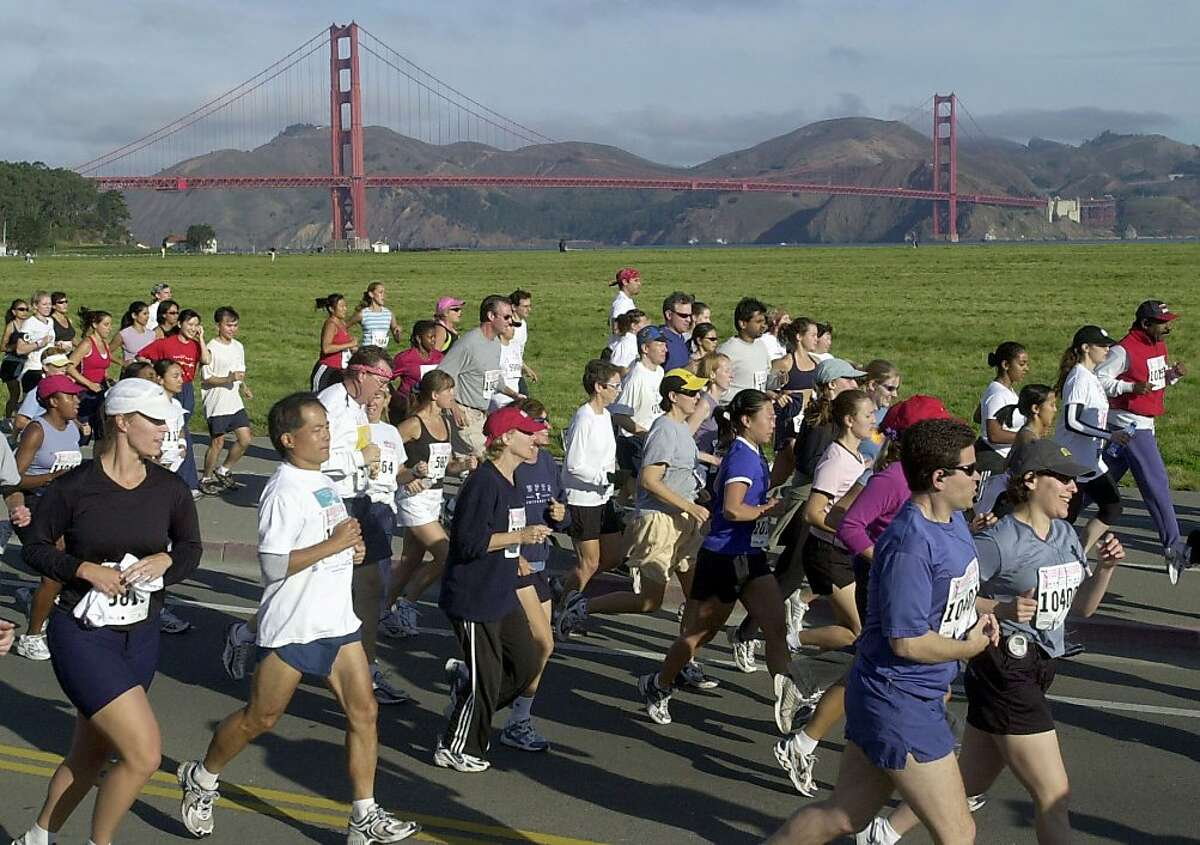 Runners embark on the 5K race with the Golden Gate Bridge providing a picturesque backdrop for the fundraising event for breast cancer research. The 13th annual Susan G. Komen Race for the Cure event in San Francisco on 9/7/03.