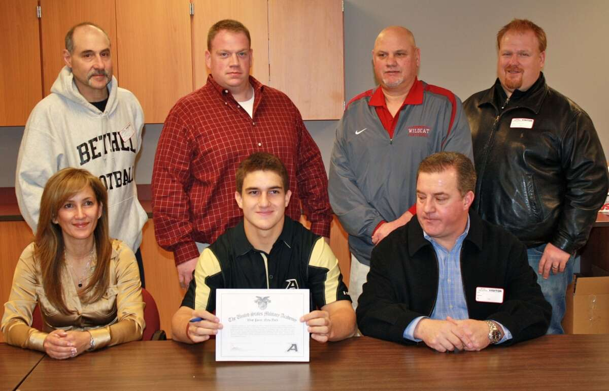 Bethel High football star Brandon Schmidt signed a National Letter of Intent to play football at West Point on Wednesday. Schmidt (front row, center) is flanked by his parents Sandra and Guillermo. Behind them are (from left) Bethel assistant coach Ned Belardinelli, Bethel head coach Jason Gill, Bethel associate head coach Bruce Martin and Bethell assistant coach Noel Gill. Schmidt, a three-year starter, collected more than 3,000 rushing yards and 1,500 passing yards in his career at Bethel High.