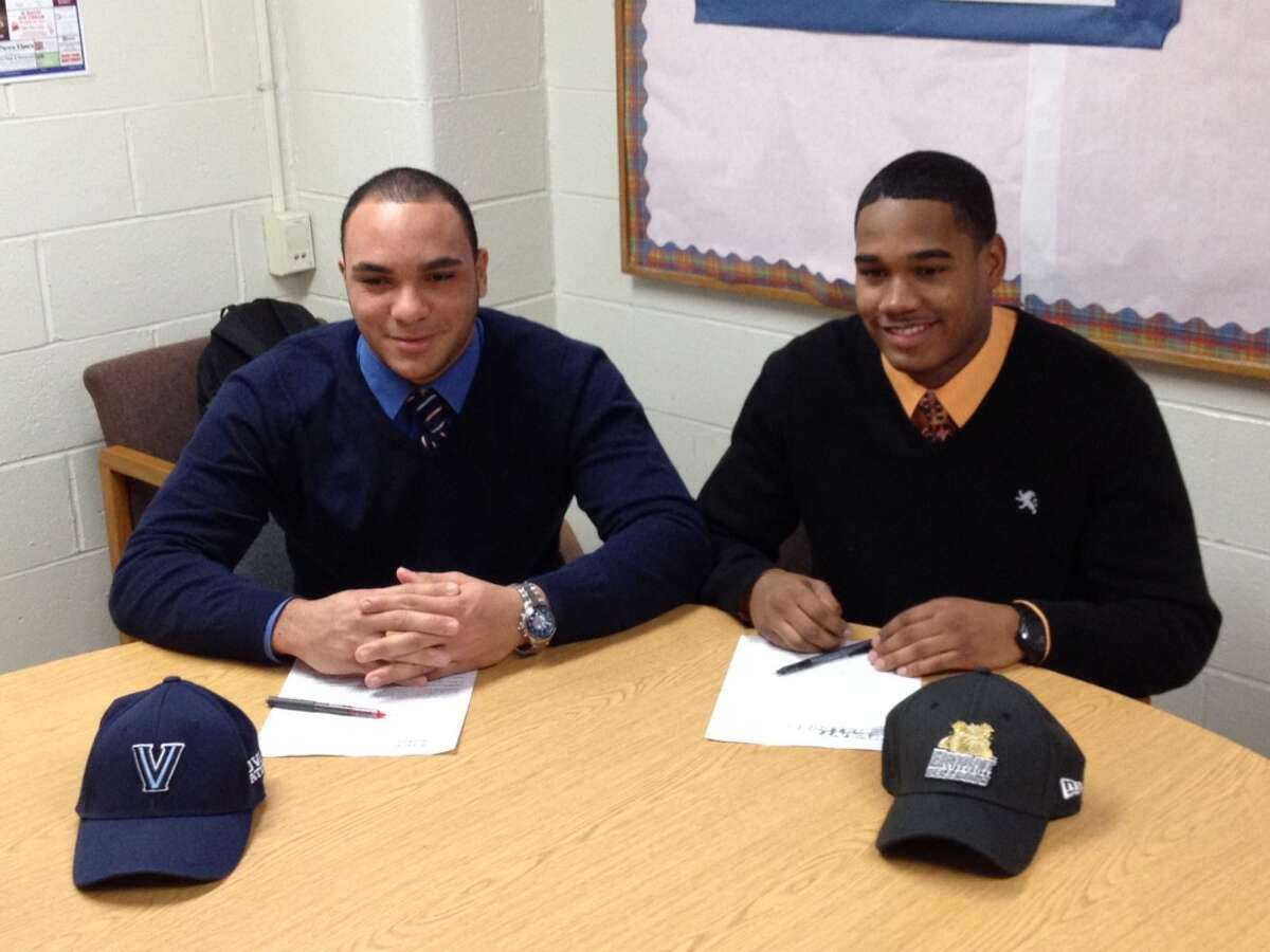 Danbury High football co-captains Austin Calitro (left) and Aaron Dixon each signed a National Letter of Intent on Wednesday to play football in college. Calitro will play for Villanova and Dixon will play for Bryant University.