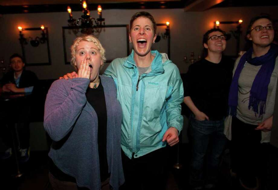 Kara Haney, left, and her partner of 8 years Kate Wertin, right, react as a bill in the Washington State Senate passes during a viewing party at The Lobby Bar in Seattle's Capitol Hill neighborhood. The Washington State Senate passed a bill that would legalize gay marriage in Washington State on Wednesday, February 1, 2012. Dozens gathered at the bar to watch the debate via TV on the senate floor. Photo: JOSHUA TRUJILLO / SEATTLEPI.COM