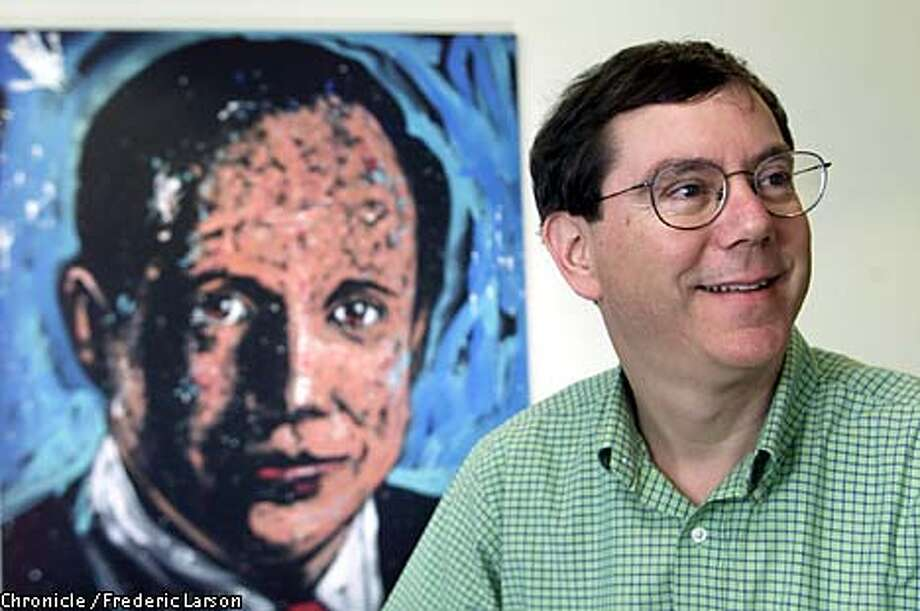 Genentech Chief Executive Officer Art Levinson stood in front of a picture of co-founder Bob Swanson, who died two years ago. Chronicle photo by Frederic Larson