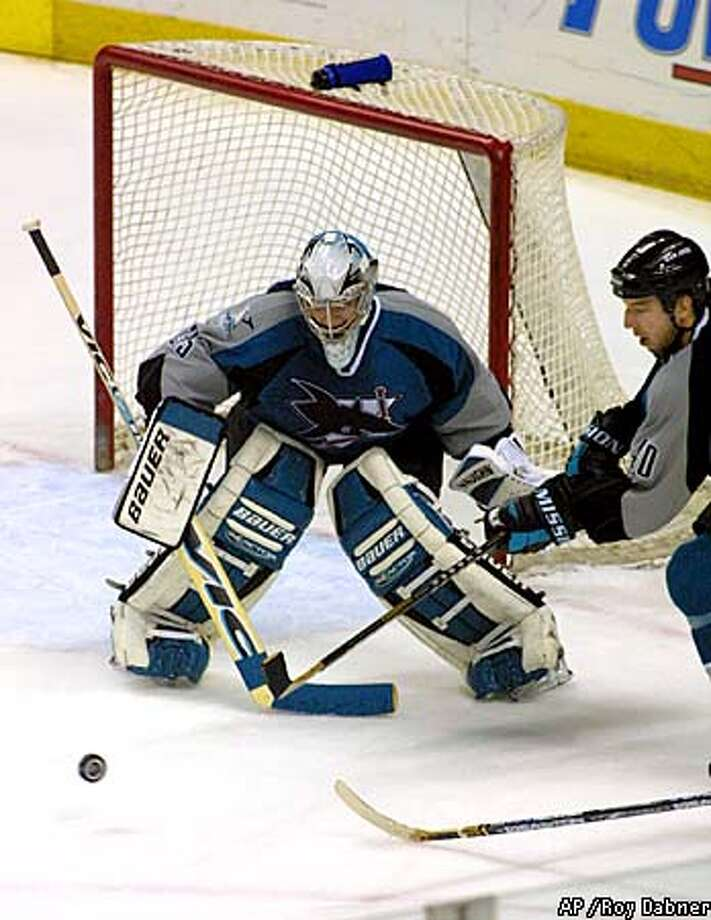 Sharks goalie Evgeni Nabokov and teammate Mike Rathje tried to corral a rolling puck last night. Associated Press photo by Roy Dabner