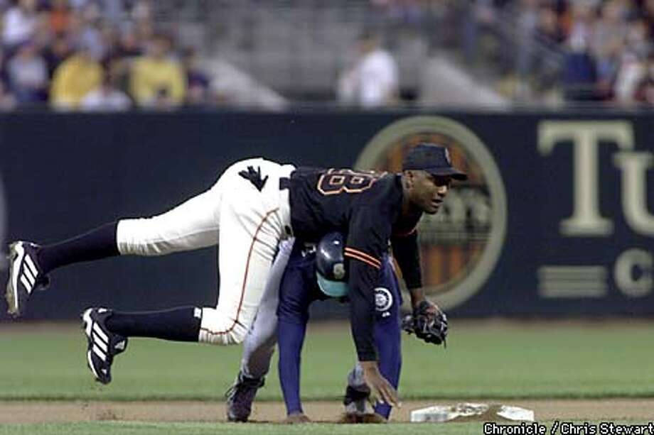 An airborne Juan Melo forced out Ramon Moreta at second base but could not turn the double play on Seattle's Bret Boone at first. Chronicle photo by Chris Stewart