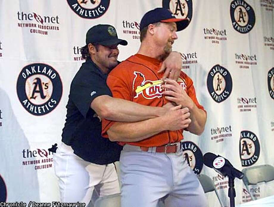 Good friends Jason Giambi and Mark McGwire, front, gave each other a hug before sitting down for a press conference before last night's game. Chronicle photo by Deanne Fitzmaurice