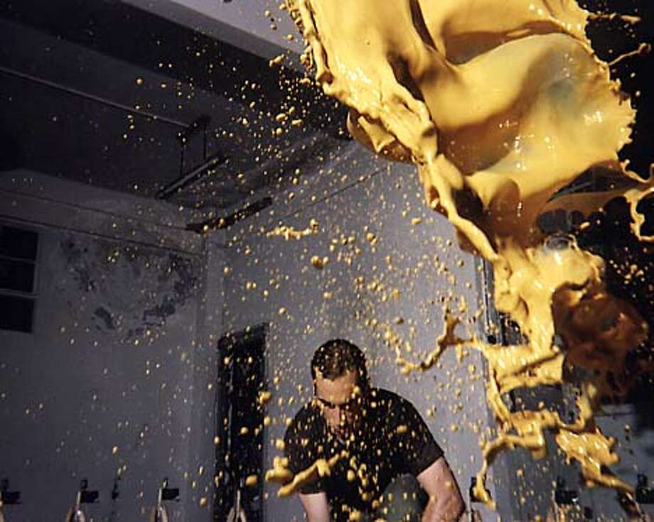 """An artist appears to dance with a spume of yellow paint in Sergio Prego's video """"Tetsuo, bound to fail"""" (1998)."""