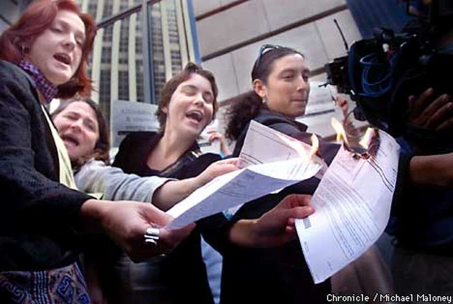 From left, Deborah James, Kirsten Moller, Shannon Wolfe and Leila Salazar (all from SF) burne their PG&E bills.  A protest sponsored by Global Exchange was held in front of PG&E headquarters on Market Street in SF at noon today. About 100 people attended to protest the recent rate hikes. A handful burned their PG&E bills in protest.  CHRONICLE PHOTO BY MICHAEL MALONEY Photo: MICHAEL MALONEY