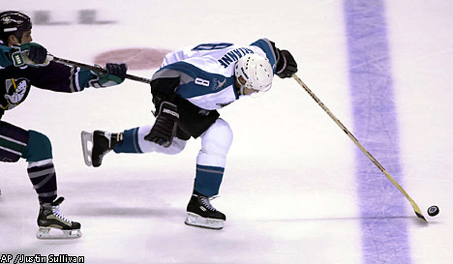 The Sharks' Teemu Selanne (8) skated toward the goal under heavy pressure from Anaheim's Samuel Pahlsson (26) in the first period. Associated Press photo by Justin Sullivan