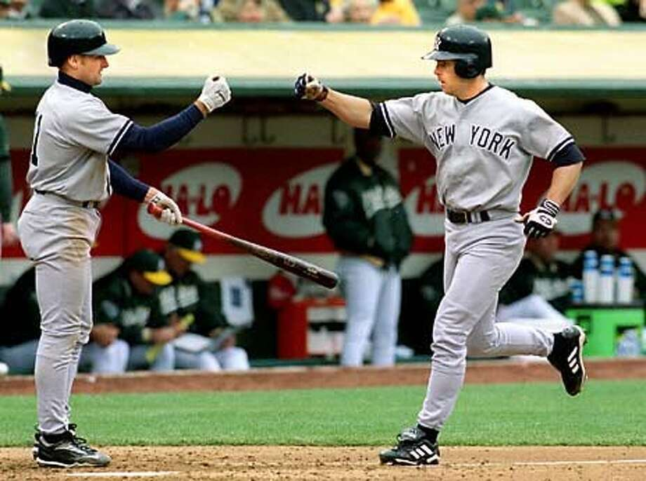 The Yankees' Chad Curtis rounds the bases and holds up his  fist to be congratulated by teammate Chuck Knoblauch after hitting a home run in the second inning against the Oakland Athletics at the Oakland Coliseum.  The Yankees won 4-0. Chronicle Photo by Robin Weiner