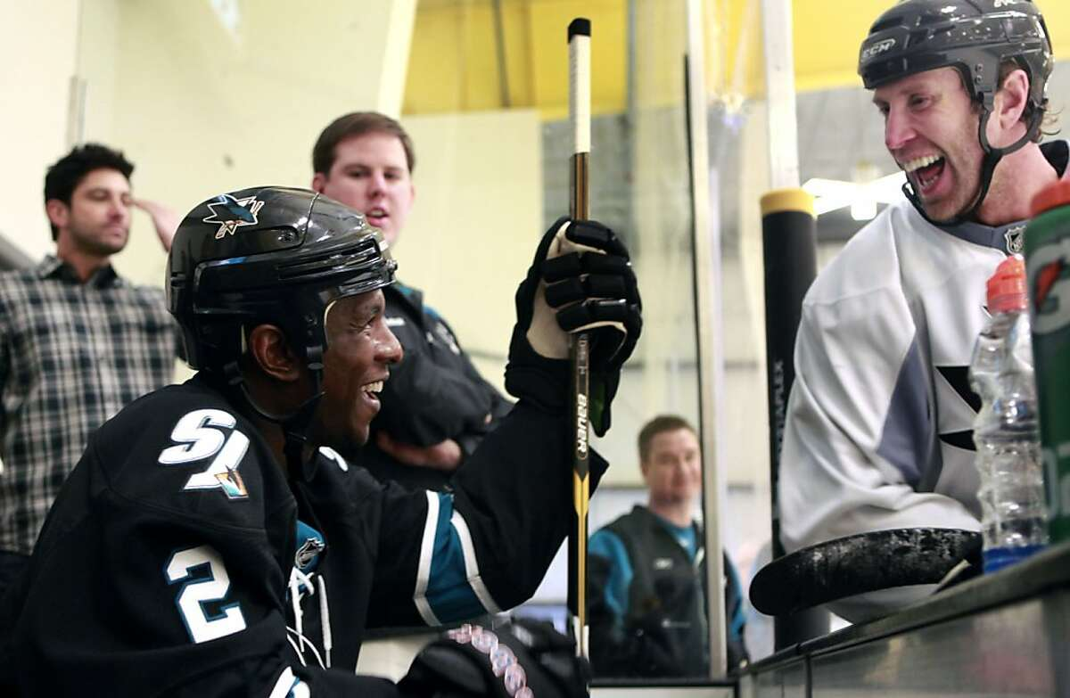 Milwaukee Brewers outfielder Nyjer Morgan left greets San Jose Sharks Joe Thornton as he sits on the practice bench waiting his turn on the ice with the Sharks Wednesday, February 1, 2012. Morgan lived a dream Wednesday when he skated with the Sharks during their practice ice in San Jose.