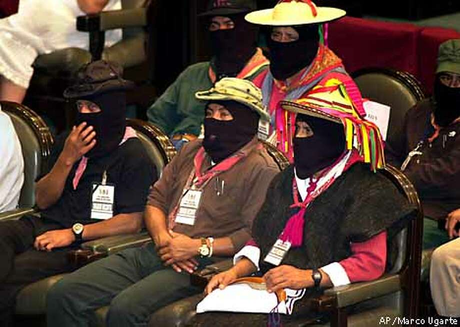 Zapatista commanders listen during a special session of the Mexican Congress in Mexico City Wednesday, March 28, 2001. Zapatista leader Subcomandante Marcos did not join the delegation, which addressed the Mexican Congress in support of an Indian rights bill. Front row, from left to right, are Zapatista commanders Zebedeo, Tacho and David. (AP Photo/Marco Ugarte) Photo: MARCO UGARTE