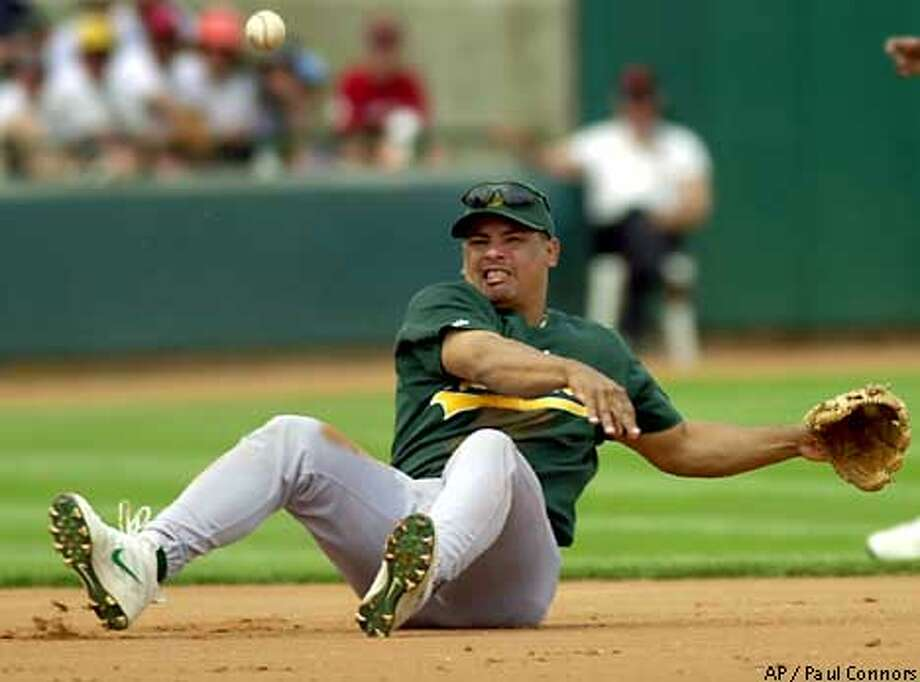 Oakland Athletics third baseman Olmedo Saenz throws to first after making a diving stop on a sharply hit ground ball in the first inning Tuesday, March 27, 2001, at Scottsdale Stadium in Scottsdale, Ariz. (AP Photo/Paul Connors) Photo: PAUL CONNORS