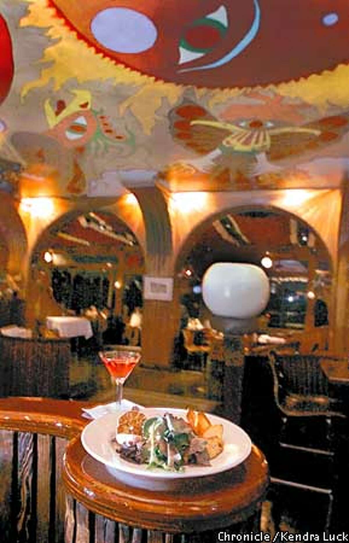 Representing the late 1960's is Horizons in Sausalito complete with hand crafted woodwork, mural on the ceiling and 40 pound round candles, here is a cocktail and a roasted garlic appetizer. (KENDRA LUCK/SAN FRANCISCO CHRONICLE)