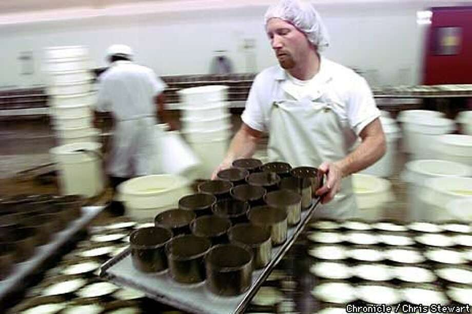 Howard Bunce readies metal forms for cheese at Rouge et Noir Marin French Cheese Co Chronicle. Photo by Chris Stewart