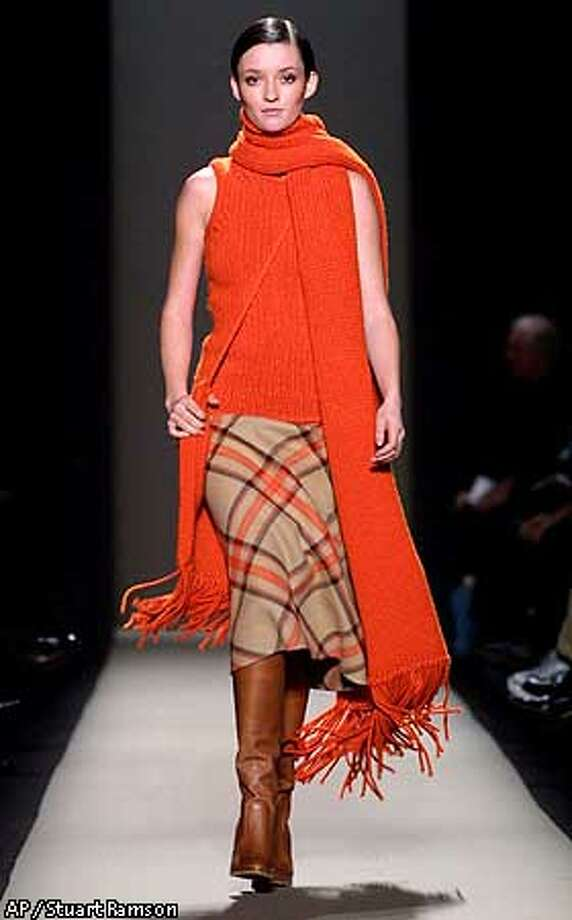 A pumpkin cashmere rope tank and matching muffler are modeled over a plaid camel and pumpkin doubleface wool riding skirt during the showing of the Fall 2001 collection of Michale Kors in New York Wednesday, Feb. 14, 2001. (AP Photo/Stuart Ramson) Photo: STUART RAMSON