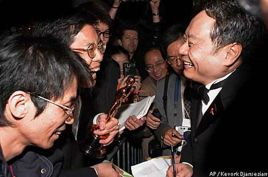 "Director Ang Lee shares a moment of laughter with reporter Frank Wang, of the Min Sheng Daily from Taipei, Taiwan, after Lee gave Wang the Oscar for Best Foreign Film for ""Crouching Tiger, Hiden Dragon,"" to hold as he signed autotgraphs outside the Sony Pictures party in Beverly Hills, Calif., after the 73rd annual Academy Awards Sunday, March 25, 2001. (AP Photo/Kevork Djansezian) Photo: KEVORK DJANSEZIAN"