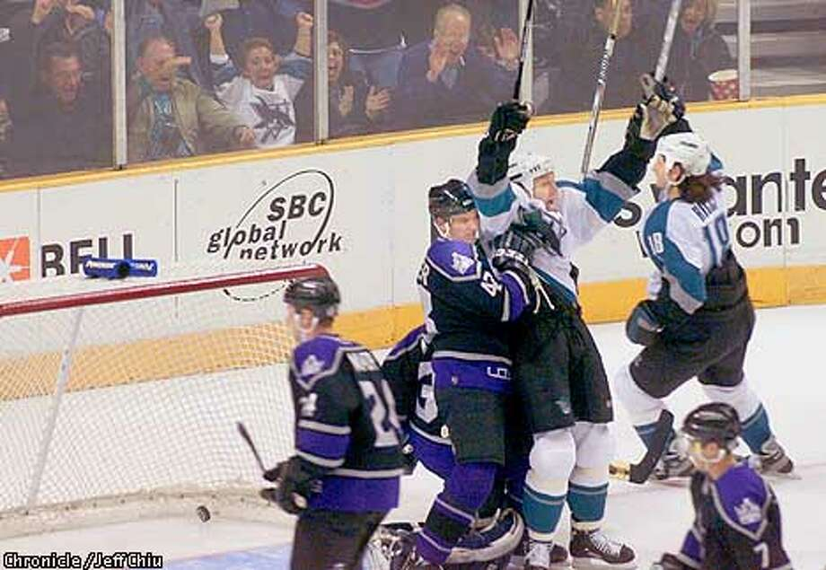 Scott Thornton and Mike Ricci (18, far right) celebrate Ricci's goal late in the second period for the Sharks to narrow the gap to 2-1 as the Sharks host the Los Angeles Kings at the San Jose Arena on Tuesday night. Photo by Jeff Chiu / The Chronicle. Photo: Jeff Chiu