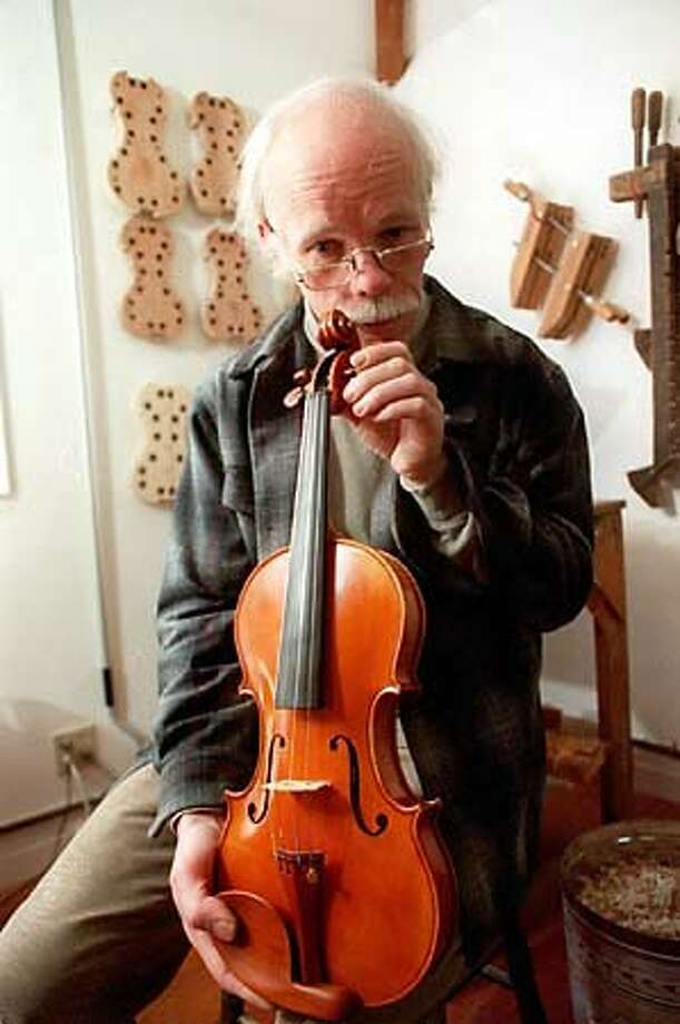 Bill Atwood, Stanford University physicist, showed off one of his violins, which have been bought by music students and professional Bay Area performers. Chronicle Photo by Thor Swift