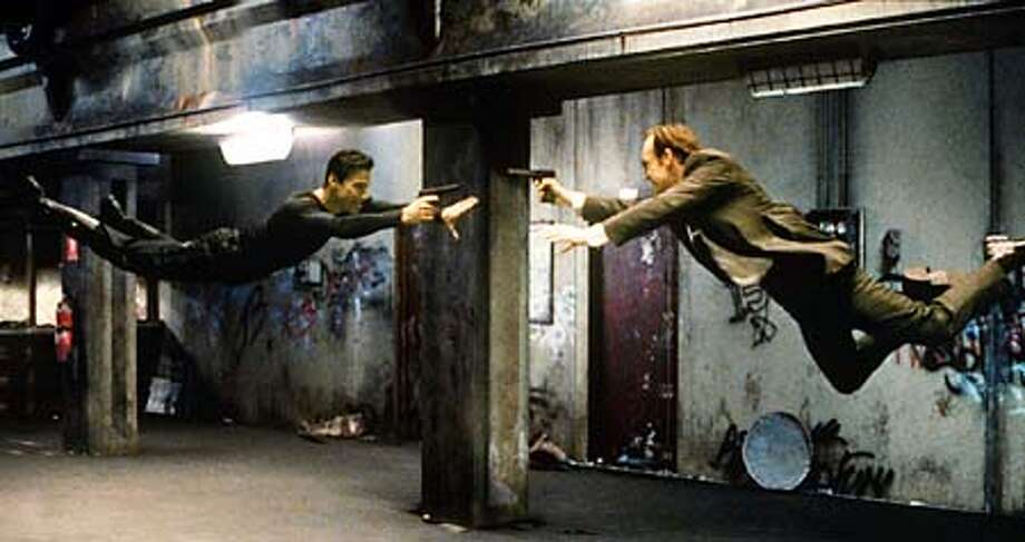 Keanu Reeves and Hugo Weaving (right) face off in a subway in ``The Matrix,'' an action-thriller about a cyberworld.