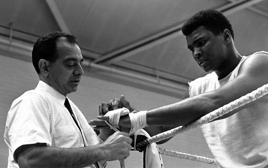 In this May 10, 1966, file photo, World Heavyweight Boxing champion Muhammad Ali, right, looks on as his hands are taped by trainer Angelo Dundee, left, before sparing with Jimmy Ellis during a training session at the Territorial Army Centre in White City, London, England. Dundee, the trainer who helped groom Ali and Sugar Ray Leonard into world champions and became one of boxing's most recognizable figures, died Wednesday, Feb. 1, 2012. He was 90. Photo: Kemp, Associated Press