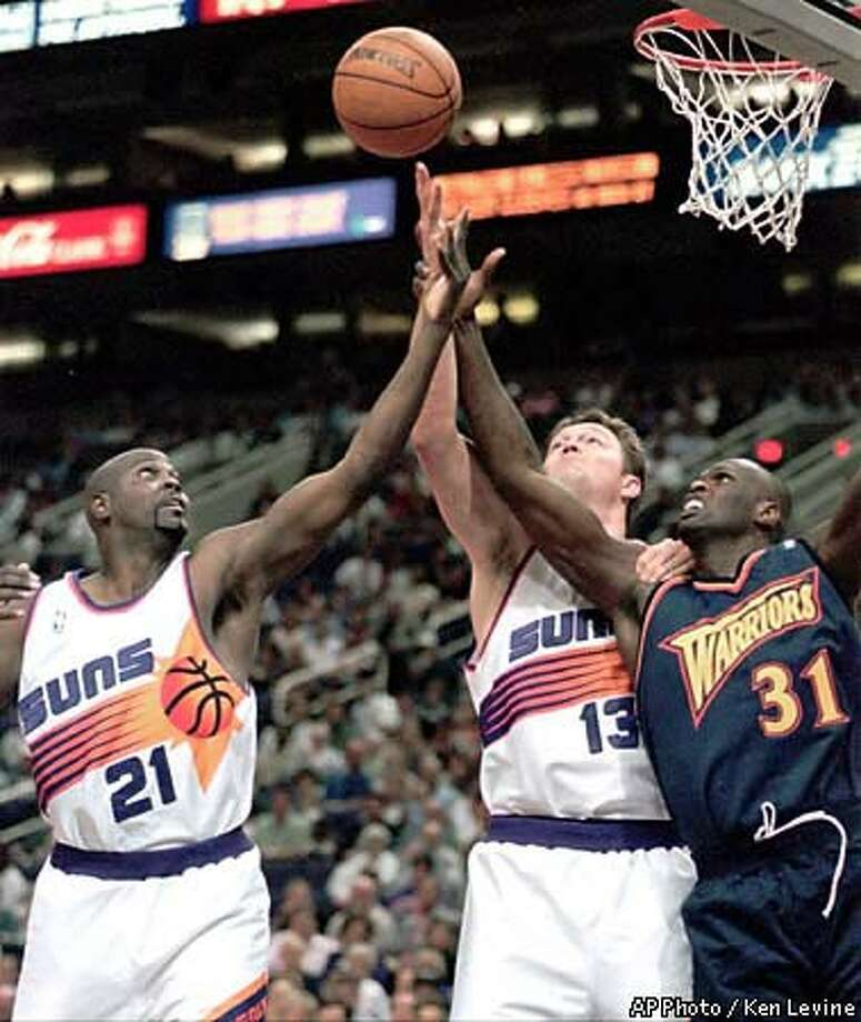 Phoenix Suns' George McCloud, left, and Luc Longley, center, battle Golden State Warriors' Adonal Foyle for a rebound during the second quarter  Wednesday, March 31, 1999, in Phoenix. Phoenix won 93-78. AP Photo by Ken Levine